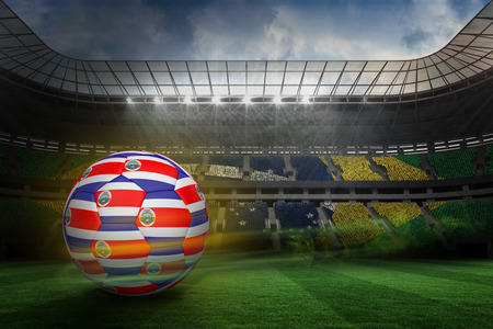 Football in costa rica colours against large football stadium with brasilian fans photo