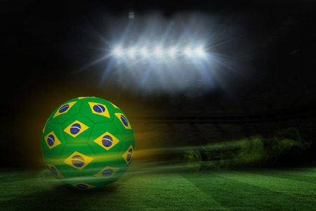 Football in brazilian colours against football pitch under spotlights photo