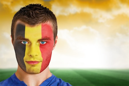 Composite image of belgium football fan in face paint against football pitch under yellow sky photo