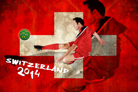 Football player in red kicking against switzerland flag in grunge effect photo