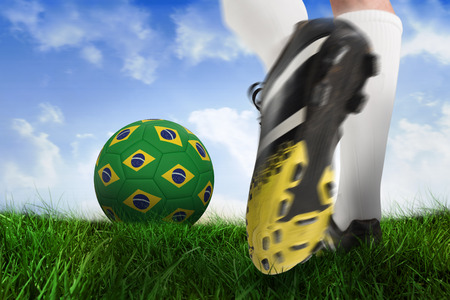 Composite image of football boot kicking brasil ball against field of grass under blue sky photo