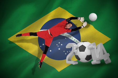 Fit goal keeper jumping up against world cup 2014 with brasil flag photo