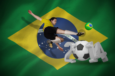 Football player in yellow kicking against world cup 2014 with brasil flag photo