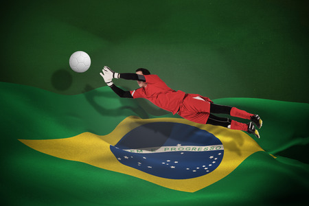 Fit goal keeper jumping up against white leather football with shadow photo