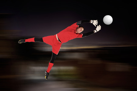 goal keeper: Fit goal keeper jumping up against blurry black background