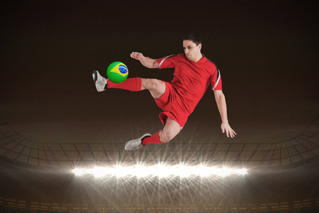 Fit football player jumping and kicking against large football stadium with spotlights at night photo