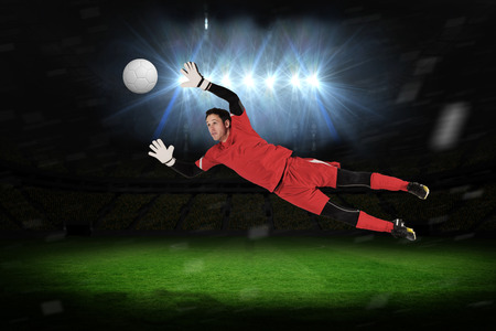 goal keeper: Fit goal keeper jumping up against football pitch under spotlights