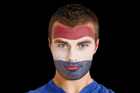 Composite image of serious young netherlands fan with facepaint against black photo