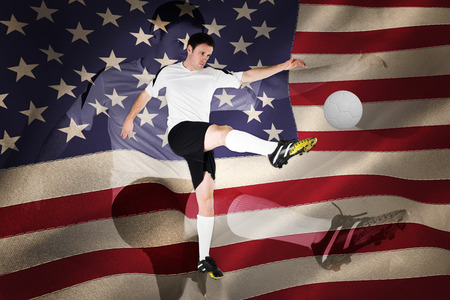 Football player in white kicking against united states of america flag photo