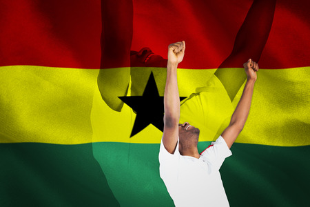 Excited handsome football fan cheering against digitally generated ghana national flag photo