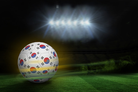 fast pitch: Football in south korea colours against football pitch under spotlights