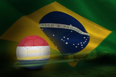 Football in holland colours against brazilian flag waving photo