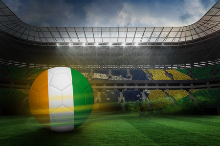 Football in ivory Coast colours against large football stadium with brasilian fans photo
