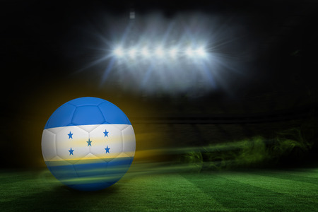 Football in honduras colours  against football pitch under spotlights photo