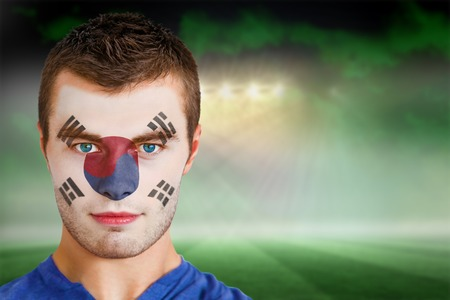 Composite image of south korea football fan in face paint against football pitch under green sky and spotlights photo