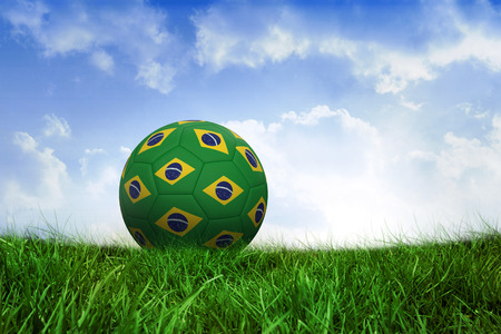 Football in brazilian colours on field of grass under blue sky photo
