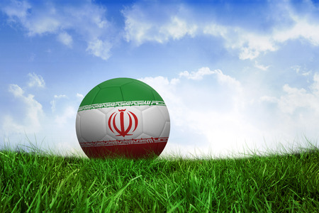 Football in iran colours on field of grass under blue sky photo