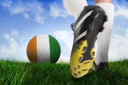 Composite image of football boot kicking ivory coast ball against field of grass under blue sky photo