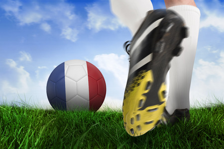 Composite image of football boot kicking france ball against field of grass under blue sky photo