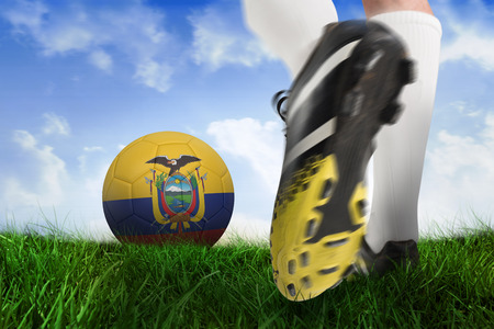 Composite image of football boot kicking ecuador ball against field of grass under blue sky photo