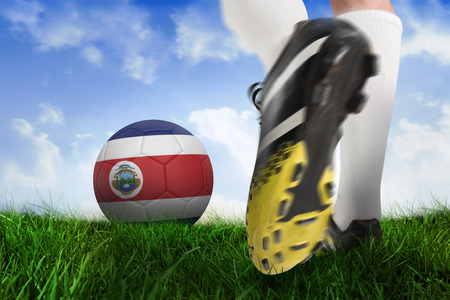 Composite image of football boot kicking costa rica ball against field of grass under blue sky photo