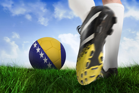 Composite image of football boot kicking bosnia ball against field of grass under blue sky photo