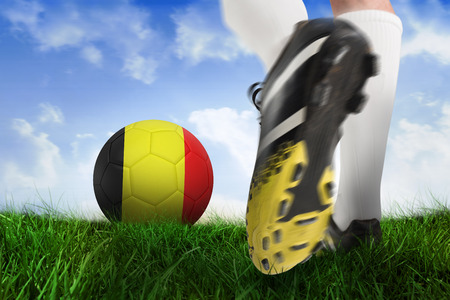 Composite image of football boot kicking belgium ball against field of grass under blue sky photo