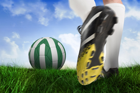 Composite image of football boot kicking nigeria ball against field of grass under blue sky photo
