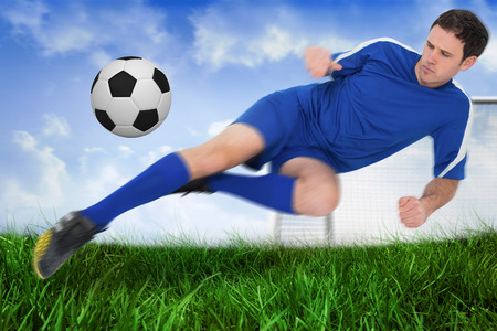 Football player in blue kicking the ball against field of grass under blue sky Stock Photo - 29076901