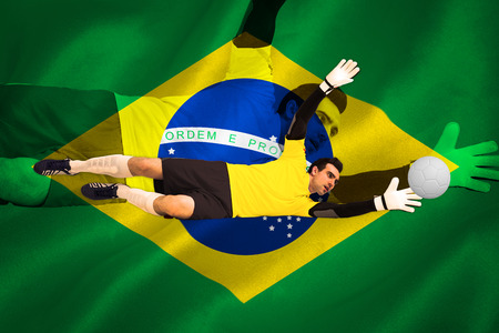 Goalkeeper in yellow making a save against digitally generated brazilian national flag photo