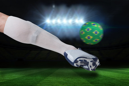Composite image of close up of football player kicking brasil ball against football pitch under spotlights photo