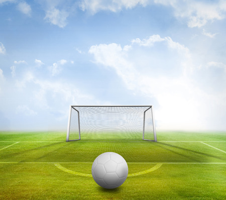 goalpost: Digitally generated white leather football against football pitch and goal under blue sky Stock Photo