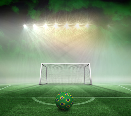 Football in brazilian colours against football pitch and goal under spotlights photo