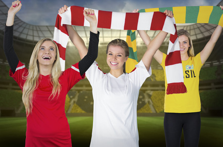 Composite image of various football fans against large football stadium with brasilian fans photo