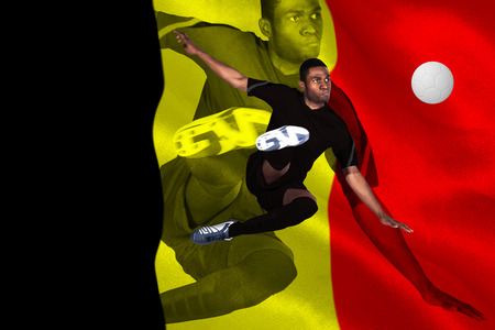 Football player in black kicking against belgium flag photo