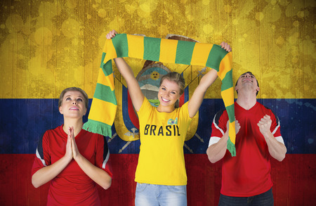 Composite image of various football fans against ecuador flag in grunge effect photo