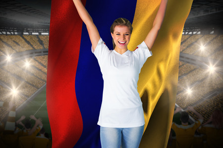 Pretty football fan in white cheering holding colombia flag against vast football stadium with fans in yellow Stock Photo