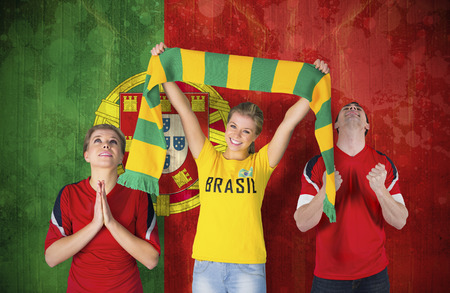 Composite image of various football fans against portugal flag in grunge effect photo