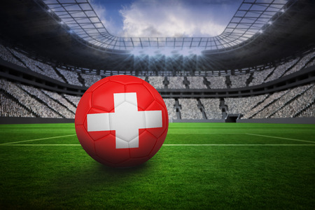 Football in swiss colours in vast football stadium with fans in white photo