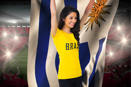 Excited football fan in brasil tshirt holding uruguay flag against vast football stadium with fans in red photo