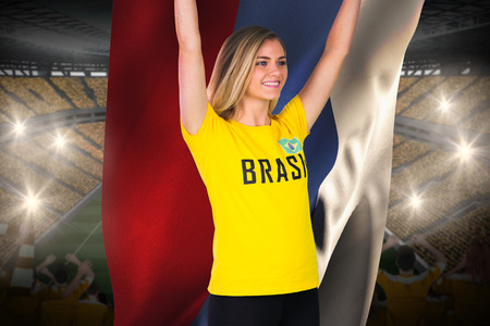 Excited football fan in brasil tshirt holding russia flag against vast football stadium with fans in yellow photo