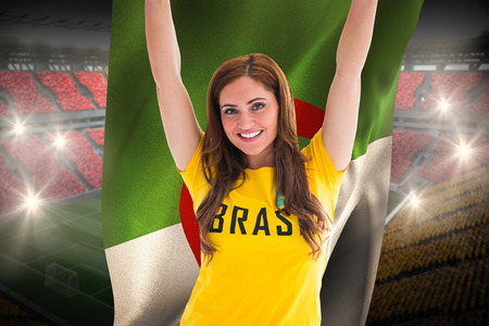Pretty football fan in brasil t-shirt holding algeria flag against vast football stadium with fans in yellow and red photo