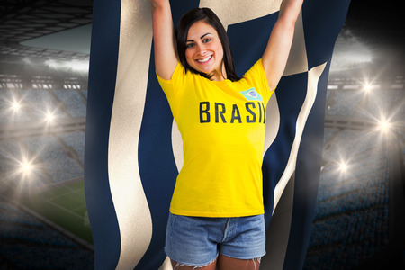 Excited football fan in brasil tshirt holding greece flag against large football stadium with fans in blue photo