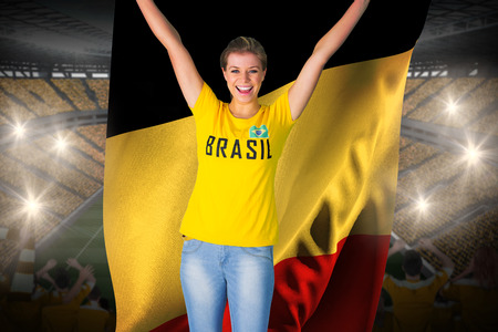 Excited football fan in brasil tshirt holding belgium flag against vast football stadium with fans in yellow photo