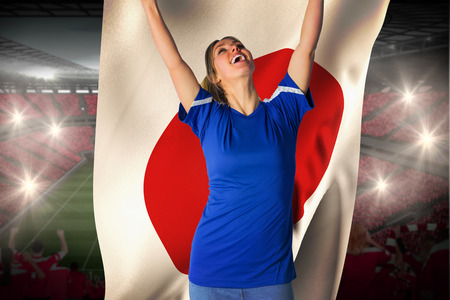 Cheering football fan in blue jersey holding japan flag against vast football stadium with fans in red photo