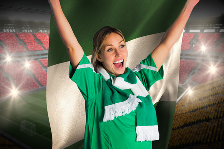 Cheering football fan in green jersey holding nigeria flag against vast football stadium with fans in yellow and red photo