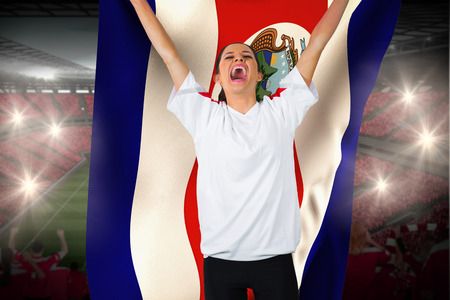 costa rica flag: Football fan in white cheering holding costa rica flag against vast football stadium with fans in red