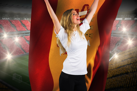 Pretty football fan in white cheering holding spain flag against vast football stadium with fans in yellow and red photo