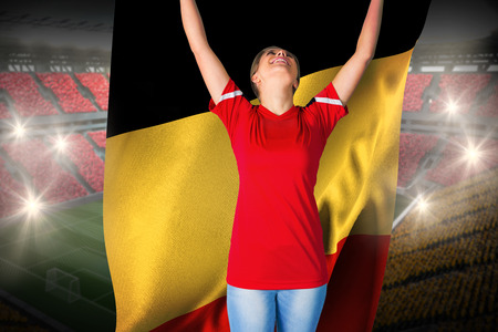 Cheering football fan in red holding belgium flag against vast football stadium with fans in yellow and red photo