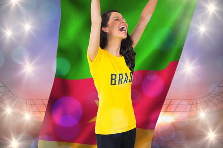 Excited football fan in brasil tshirt holding cameroon flag against large football stadium under purple sky photo